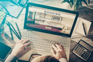 Man Booking Hotel on Laptop