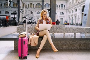 Woman Uses Laptop Waiting with Luggage